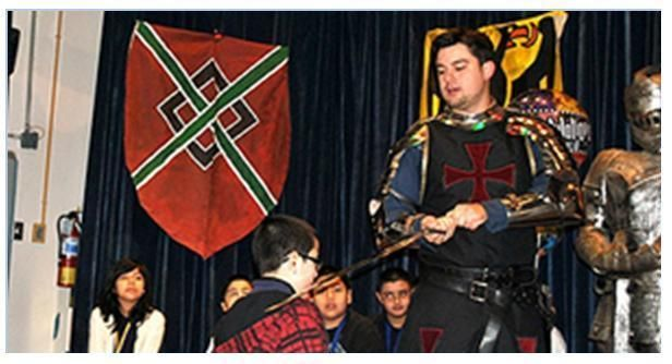 A knight placing a sword on the shoulder of a student.