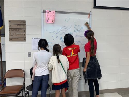 MIMS students writing on whiteboard