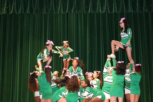Cheerleaders organizing a pyramid on stage.
