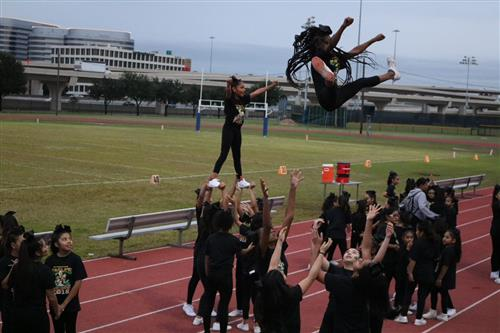 Cheerleaders performing lifts and jumps.