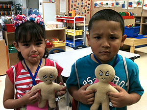 """Farias ECC students model the emotions represented by the """"Feeling Buddies"""" they are holding. """"Feeling Buddies"""" help children recognize and name the feelings they are experiencing, so that they can better deal with emotional upsets."""