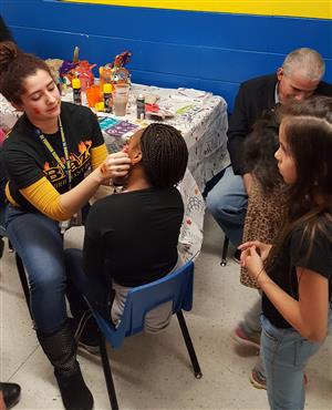 Mrs. Barreto-Paz painting faces.
